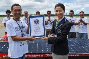 ソーラーカー世界最速のギネス認定証をウカソヴァさん(手前右)から授与された篠塚さん(同左)=22日、下地島空港