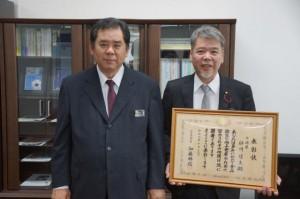 砂川靖保健医療部長(左)に食品衛生関係功労者の厚生労働大臣表彰受賞を報告した砂川靖夫社長(右)=24日、県庁