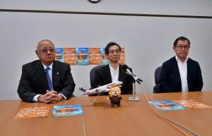 夏期スケジュールとスーパースターセールについて説明する中村会長(中央)と下地市長(左)。右は伴野社長=6日、市役所平良庁舎