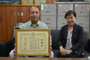 玉城知事から贈られた感謝状を手にする武島さん。右は大宮校長=20日、伊良部高校