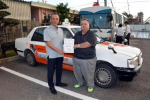 宮古タクシーパトロール隊として委嘱を受けた県ハイヤー・タクシー協会宮古支部の下地支部長(左)。右は山里克洋副支部長=19日、宮古島警察署