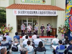 地域住民や関係者らが見守る中でテープカットが行われた=25日、字塩川の同施設